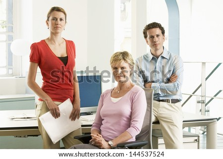 Portrait of middle aged businesswoman with team at office desk - stock photo
