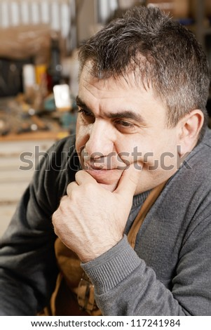 Portrait of middle-aged caucasian man in apron looking sideways - stock photo