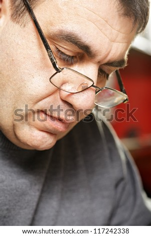 Portrait of middle-aged caucasian man in eyeglasses looking down - stock photo
