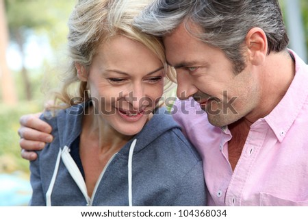 Portrait of middle aged couple looking at each other - stock photo