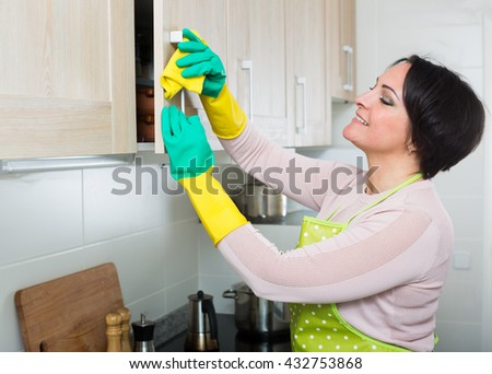 Portrait of middle aged female cleaning kitchen cupboards at home - stock photo