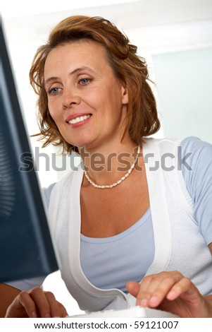 Portrait of middle-aged female typing on computer keyboard - stock photo