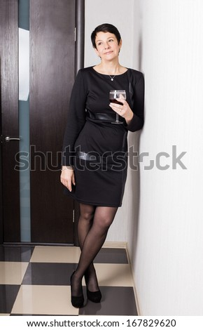 Portrait of middle aged female with flute of red wine - stock photo