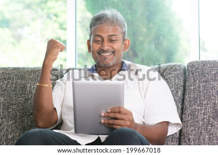 Portrait of middle aged Indian man reading on digital tablet computer and cheering at home. - stock photo