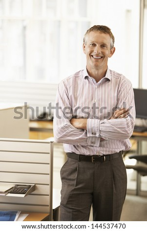 Portrait of middle aged male executive with hands folded smiling in office - stock photo