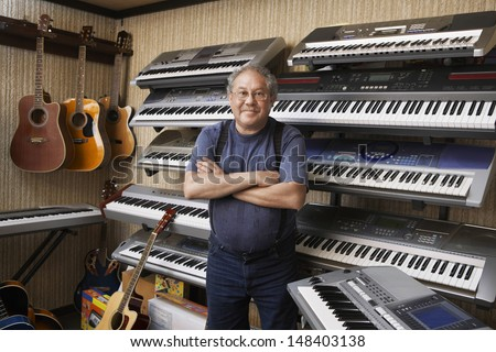 Portrait of middle aged male music store owner standing arms crossed - stock photo