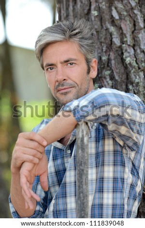 Portrait of middle-aged man standing against tree - stock photo