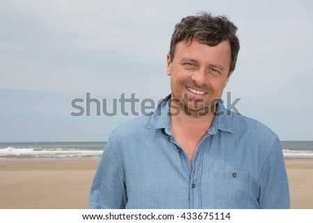 Portrait of middle aged man standing at the beach smiling under blue sky