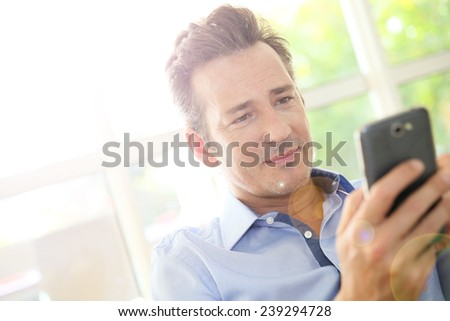 Portrait of middle-aged man using smartphone - stock photo