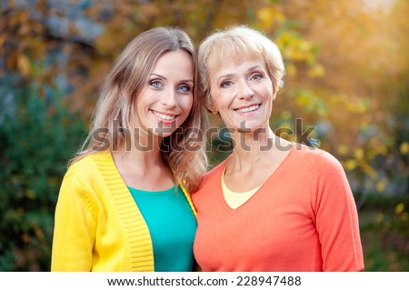 Portrait Of Middle aged Mother And her Adult Daughter smiling at camera outdoors - stock photo