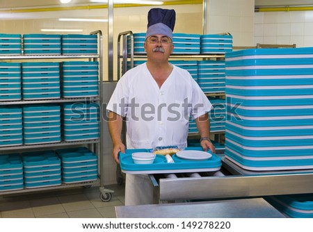 Portrait of middle aged porter with plastic trays in hospital kitchen - stock photo