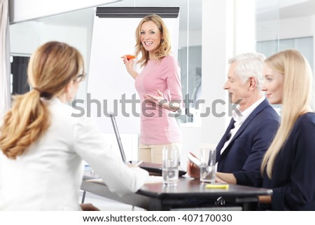 Portrait of middle aged professional woman presenting new business idea to her coworkers.  - stock photo
