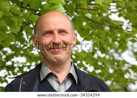 portrait of middle-aged  smiling  man outdoor - stock photo