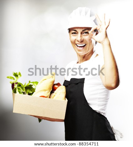 portrait of middle aged woman carrying food in a box indoor - stock photo
