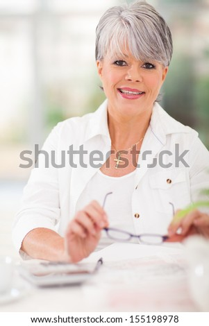 portrait of middle aged woman doing home finances - stock photo