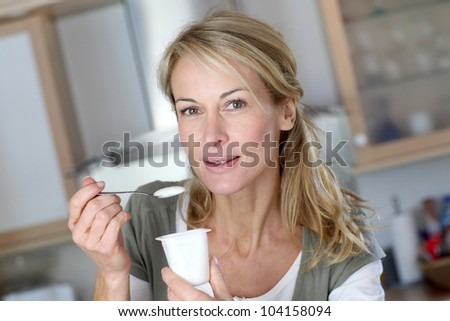 Portrait of middle-aged woman eating yoghurt - stock photo