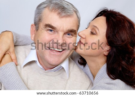 Portrait of middle aged woman embracing happy man while he laughing