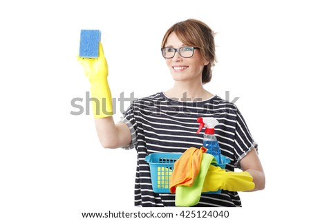 Portrait of middle aged woman holding a spray bottle and sponges in her hand while cleaning glass. Isolated on white background.  - stock photo