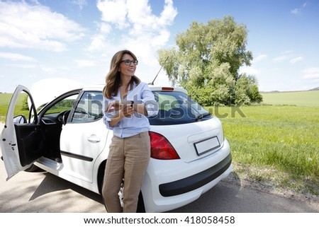 Portrait of middle aged woman looking her watch while standing on the road alongside her broken down car and waiting for helping.