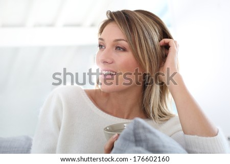 Portrait of middle-aged woman relaxing at home - stock photo