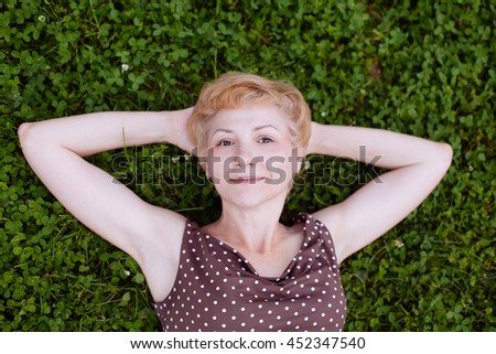 Portrait of middle aged woman smiling on the grass