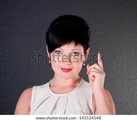 portrait of middle aged woman thinking over black background - stock photo