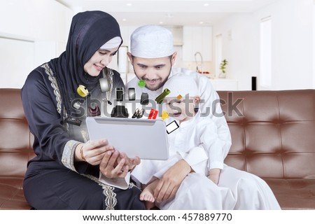 Portrait of middle eastern family sitting on the sofa while shopping online with tablet at home