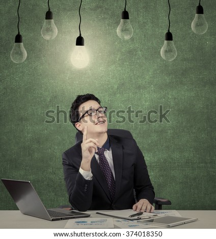 Portrait of middle eastern young businessman working with laptop on desk and looks get idea under light bulb - stock photo