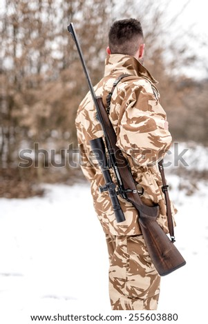 Portrait of military army man carrying a sniper rifle, for battlefield operations - stock photo