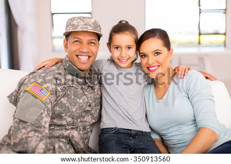 portrait of military family sitting on the couch at home - stock photo