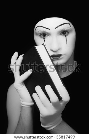 Portrait of  mime in white gloves with the book