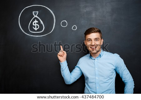 Portrait of minded man pointing on his mind about money. suited. young businessman - stock photo
