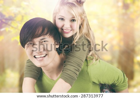 Portrait of mixed race couple enjoy summer holiday and having fun together in the park