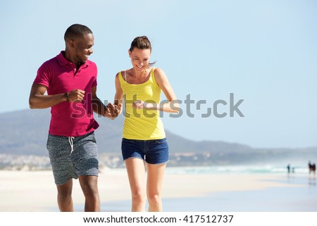 Portrait of mixed race couple running together on the beach