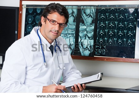 Portrait of mixed race male radiologist sitting at desk with clipboard - stock photo