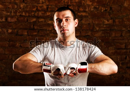 portrait of mma fighter in boxing pose against brick wall - stock photo