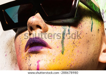 Portrait of model wearing sunglasses. Close-up portrait of young woman with unusual makeup. Model posing with paint drops over her face. Creative makeup.  - stock photo