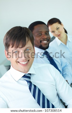 Portrait of modern business team looking at camera with male leader in front