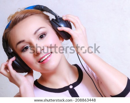 Portrait of modern businesswoman young woman or student girl with headphones listening to music mp3 relaxing or learning language. - stock photo