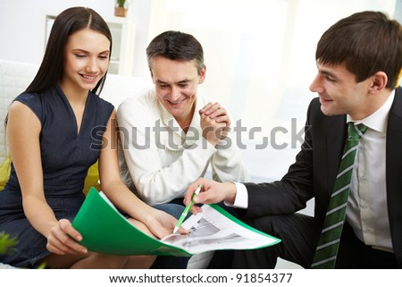 Portrait of modern couple listening to manager explanation of mortgage conditions - stock photo