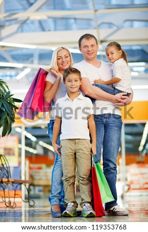 Portrait of modern family with paperbags looking at camera in the mall