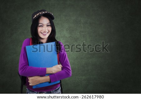 Portrait of modern female student standing in the class while smiling at the camera in front of chalkboard - stock photo