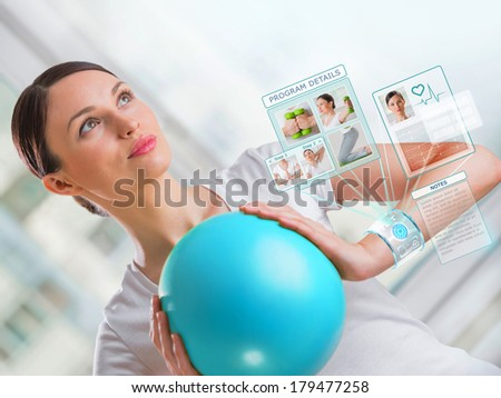 Portrait of modern healthy woman wearing smart watch device with touchscreen doing exercises - stock photo