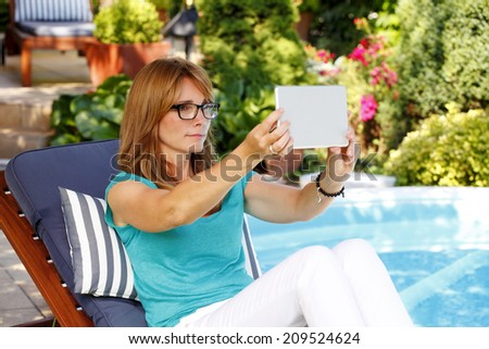 Portrait of modern mature woman sitting at garden and taking self portrait with digital tablet.  - stock photo