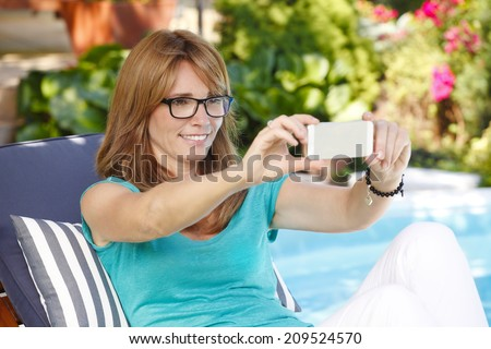 Portrait of modern mature woman sitting at garden and taking self portrait with smart phone.  - stock photo