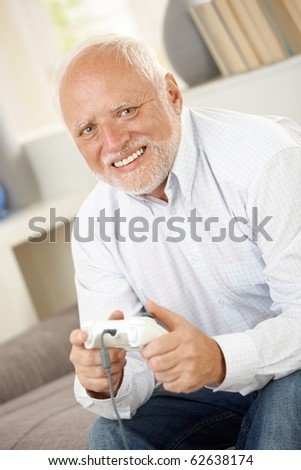 Portrait of modern senior playing computer game, smiling, looking at camera.? - stock photo