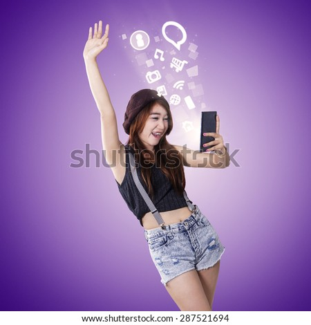 Portrait of modern teenage girl with casual clothes using smartphone and looks happy - stock photo