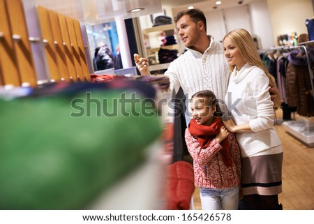 Portrait of modern young couple and their daughter spending time in the mall