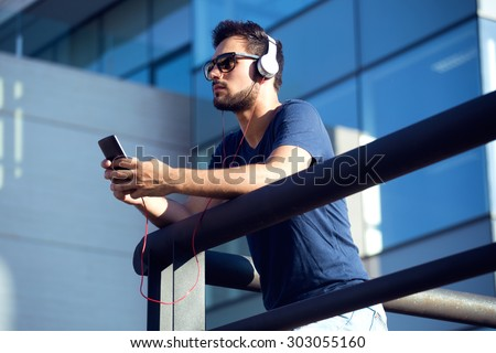 Portrait of modern young man listening to music with mobile phone in the street. - stock photo