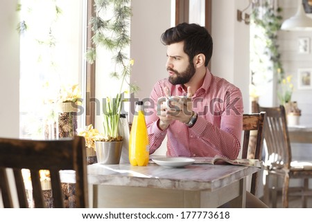 Portrait of modern young man sitting at table in coffee shop.  - stock photo